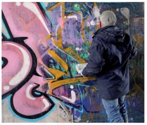Vrstvený atak graffiti na kamenném podkladu.