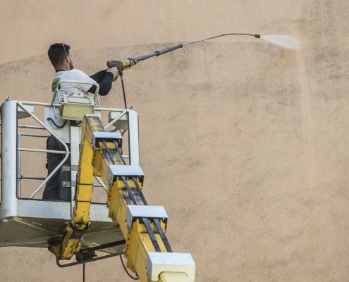 Bezdotyková aplikácie a čistenie fasády - Profesionál z Umyjemto umýva znečistenú fasádu za pomocou zvdihací plošiny